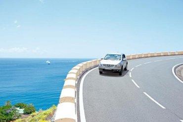 auto idúce po ceste pri morskom pobreží