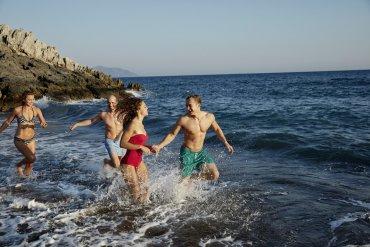 partia mladých ľudí sa zabáva v mori