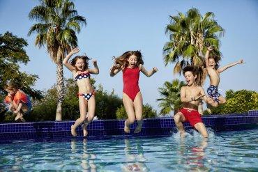 deti skáčuce do bazéna na dovolenke